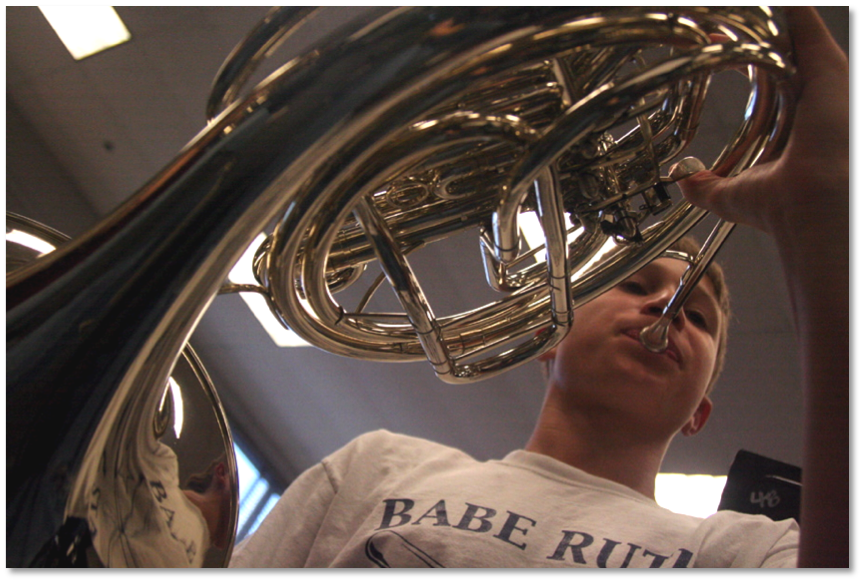 The strong curves of the instrument lead to the boy's face.